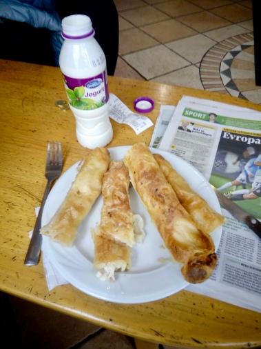 assortment of burek: cheese, potato, ham and cheese, cabbage with accompanying yogurt drink. The proper way to eat is to take a bite and follow up with a sip while the food is still in your mouth.